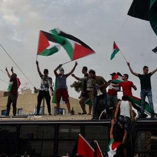 Διαδηλωτές ανεμίζουν σημαίες της Παλαιστίνης πάνω στις κλούβες των ΜΑΤ μπροστά στη σιονιστική πρεσβεία. Φωτό Ε.Α.