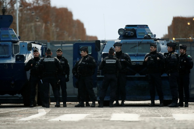 "French Gendarmes stand next to armoured vehicles in place on the Champs-Elysees Avenue during a national day of protest by the ""yellow vests"" movement in Paris"
